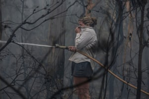 Local Lucy Sharman hoses down bush by a neighbours property that is on fire by Moss Vale Road, Kangaroo Valley.