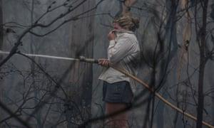 Lucy Sharman hoses down still-burning bushland