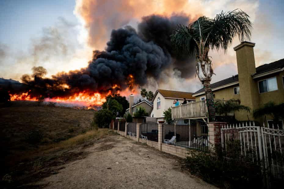 Residents watch flames from the Blue Ridge fire creep closer to their homes on 27 October in Butterfield Ranch, California.