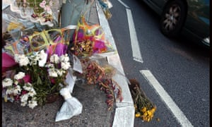 Flowers tied to street sign near the site of a fatal traffic accident.