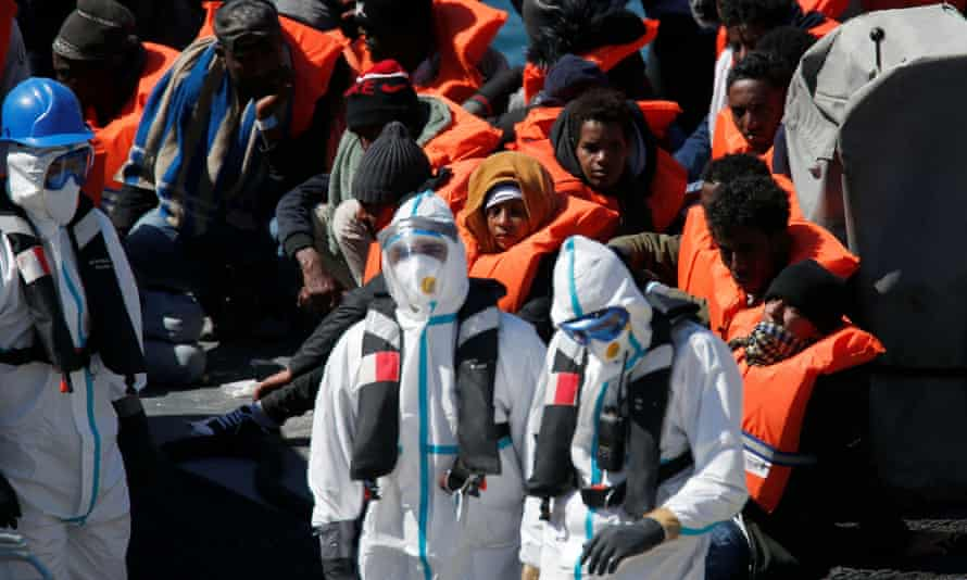 Armed Forces of Malta soldiers in protective clothing against possible coronavirus infection with rescued migrants.