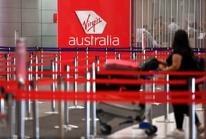 A woman pushes a trolley in a Virgin Australia check-in area