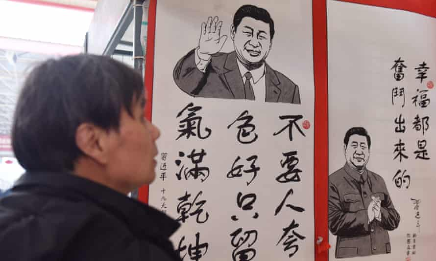 A man looks at a poster quoting the thoughts of President Xi Jinping, in Beijing.