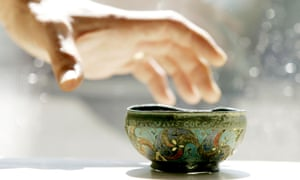 A member of staff holds the Staffordshire Moorlands Pan at its unveiling at the British Museum in London, August 16, 2005