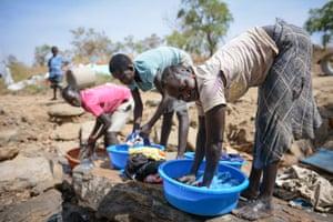Apai Regina, 25, washes clothes in Bidi Bidi settlement