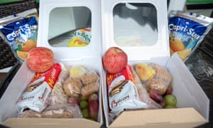 Two identical packed lunches side b y side featuring a sandwich, snack, biscuit, fruit and orange drink