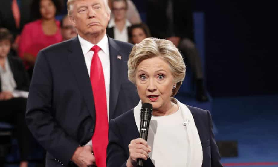 Donald Trump listens as Hillary Clinton answers a question from the audience at Washington University in St Louis in October 2016.