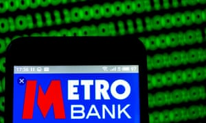 a metro bank logo on a smartphone amid a backdrop of binary computer images
