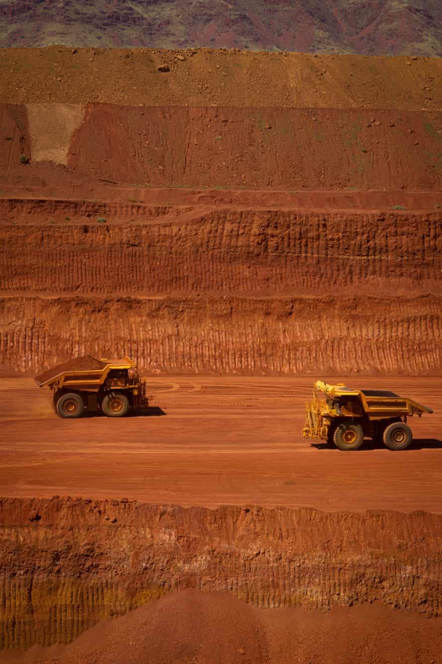 Autonomous haul trucks drive through a pit at a Rio Tinto iron ore mine in the Pilbara.