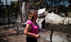 A woman walks in front of her destroyed house in the village of Neos Voutzas, near Athens.
