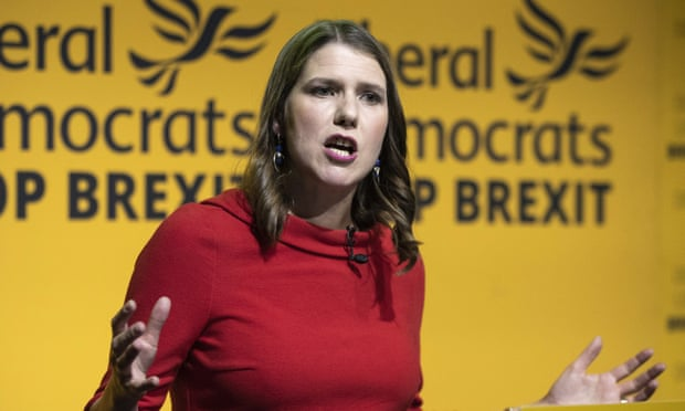 Image shows Jo Swinson delivering a speech in front of Liberal Democrat banners
