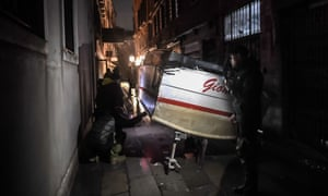 A stranded taxi boat is pictured in an alleyway after being washed away during an exceptional 'Alta Acqua'