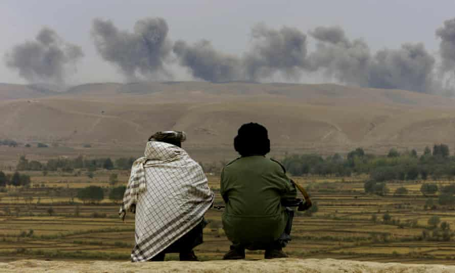 Northern Alliance soldiers watch as smoke rises from explosions on Taliban positions near Ai-Khanum village, Afghanistan in 2001.