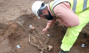A man in a hard hat and hi-vis clothing bending over a partly unearthed skeleton in the ground