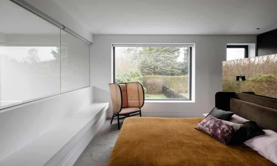 'I wanted this to be an un-shouty house': a bedroom with mirror to reflect the arboreal view.