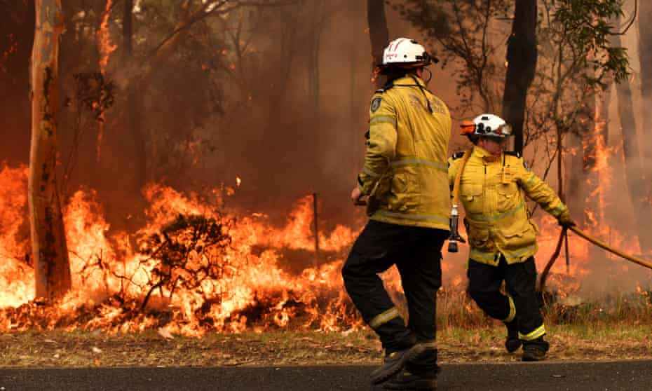 NSW Rural Fire Service firefighters battle a blaze on the central coast. Many of the sleep-deprived volunteer crew are taking leave without pay and are stretched beyond endurance by the weeks-long bushfires.