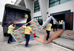 Bangkok. Workers carry mattresses prepared as beds for patients amid the surge of COVID-19