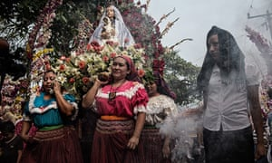 Women carry a statue of the Virgin Mary during the Palms Festival through Panchimalco's streets