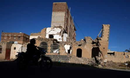 A motorcyclist drives past a destroyed building in Sana'a