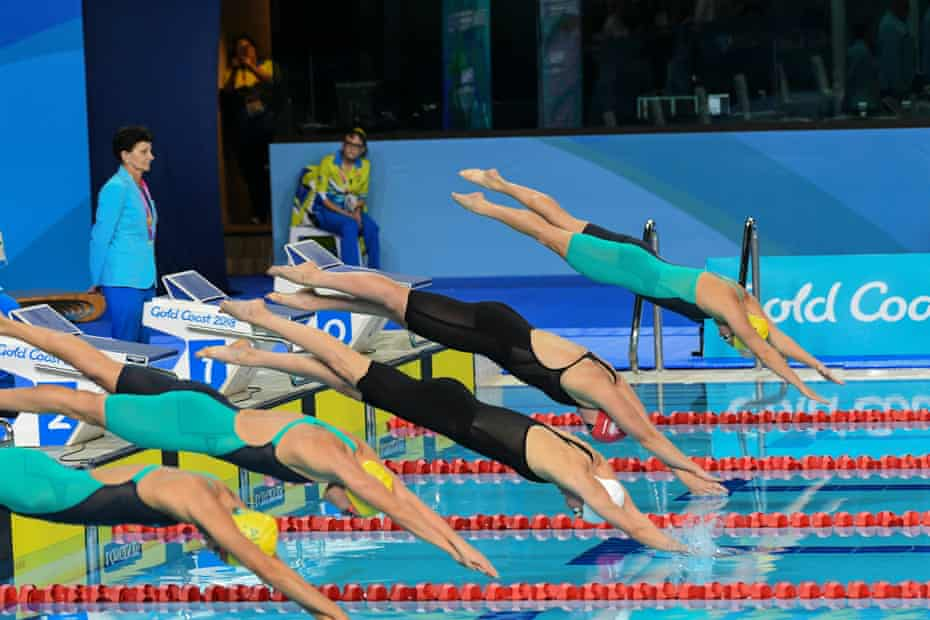 Swimmers dive into the pool at the start of a race.