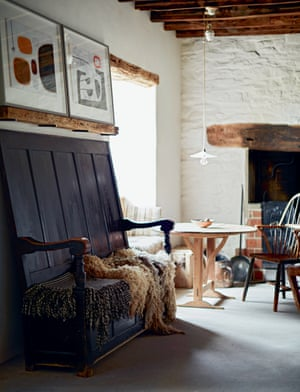 'We are forever rescuing and reusing, repairing and rethinking everything': a light-filled room with wooden furniture and sheepskin throws.