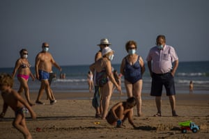 People wear face masks at the beach in Barbate, Cadiz province, south of Spain, on Saturday, 25 July, 2020.