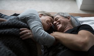 Affectionate, romantic senior couple cuddling in bed
