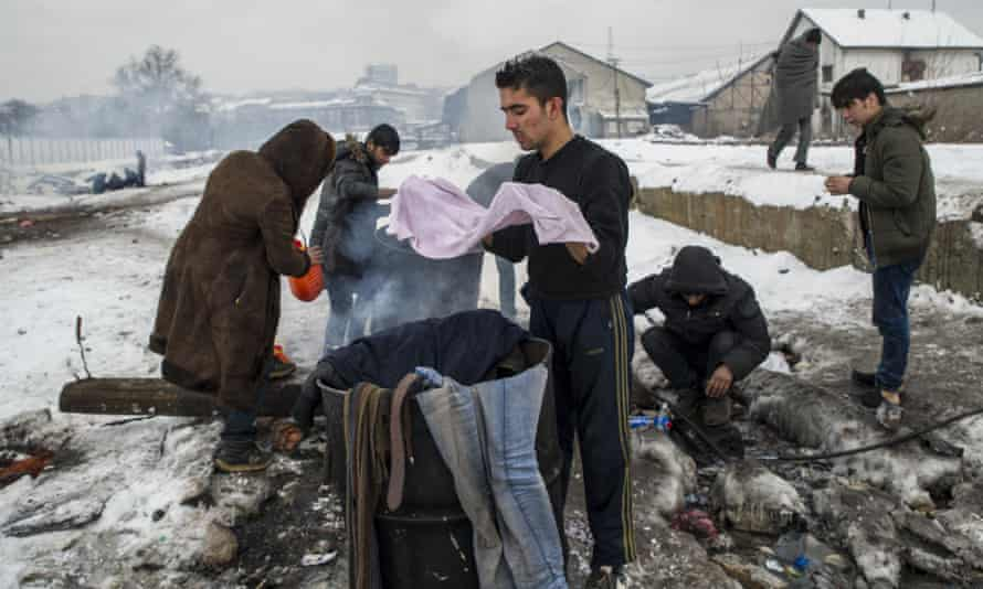 Refugees wash themselves and their clothes over a barrels of water heated by fire in the snow in Belgrade.