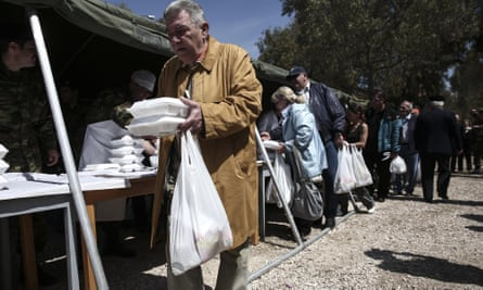 People queue for food at a military camp in Athens.
