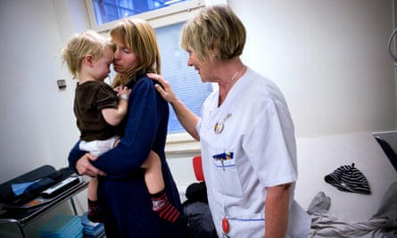 A nurse speaks to a mother and child in the emergency unit of Astrid Lindgren's Children's hospital in Stockholm