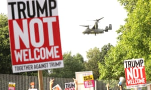 Protesters in Regent's Park, London, as a US military helicopter flies overhead.