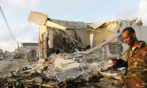 A Somali soldier walks near destroyed buildings after a suicide car bomb on Friday night in Mogadishu.