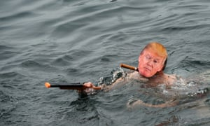 A man in a Donald Trump mask  and a toy gun swims   during the  Christmas Cup swimming race in   Lake Geneva,  Switzerland.