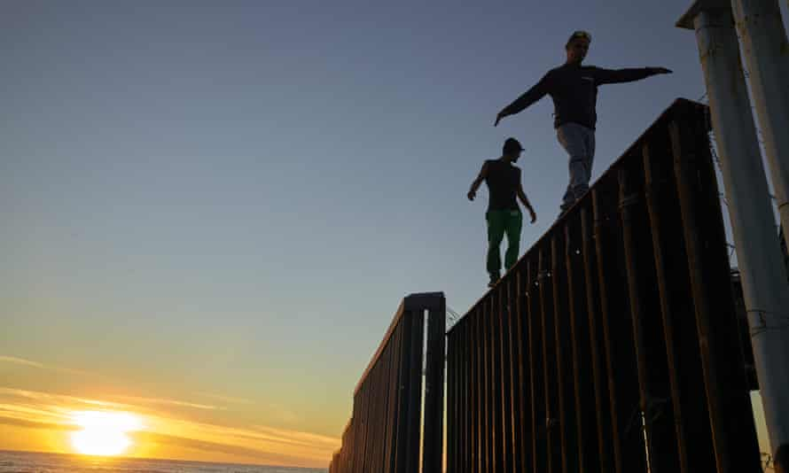 Migrants on the the border structure separating Mexico and the USA near Tijuana.
