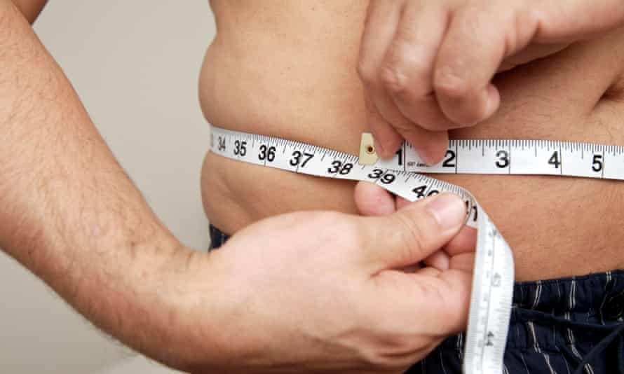 Close-up of man measuring waist with tape measure.