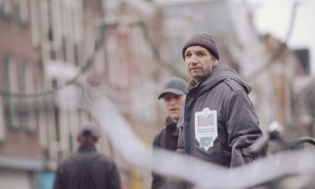 A homeless man wears a contactless payment jacket from Helping Heart.
