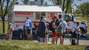 A Salvation Army EMS vehicle is setup as a cooling station as people lineup to get into a splash park while trying to beat the heat in Calgary, Alberta