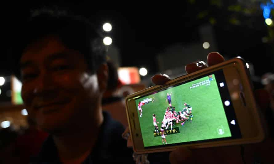 A fan enjoys watching Japan v South Africa on his mobile phone during the 2019 Rugby World Cup
