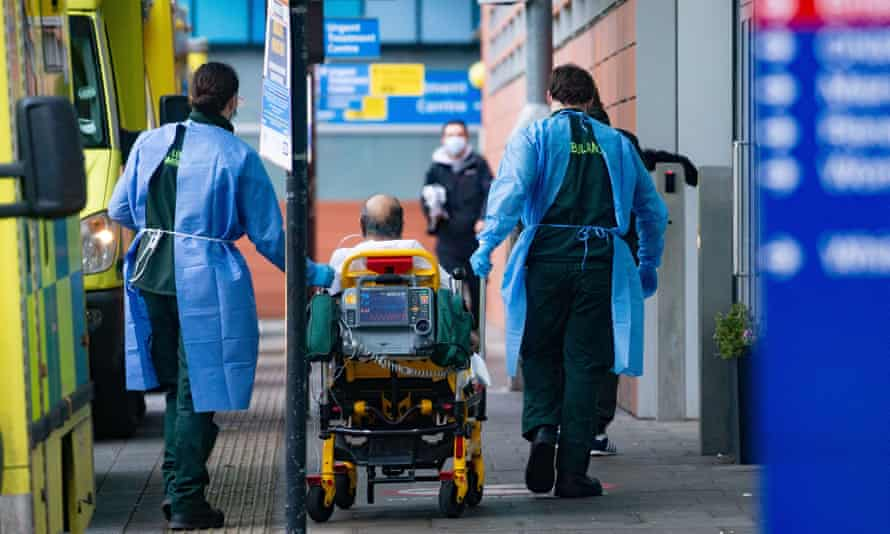 Healthcare workers bring a patient from the ambulance to the Royal London hospital.