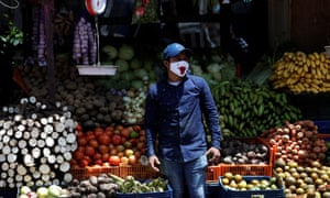 A fruit and vegetables vendor wears a mask as he waits for customers at his stall on Central Avenue in Panama City, Panama, 4 June 2020.