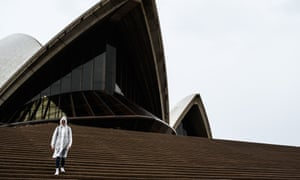 A lone tourist descends the steps of the Sydney Opera House in the rain in Sydney, Monday, 16 March 2020.