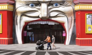 A family walk past the entrance to Luna Park in the Melbourne during lockdown