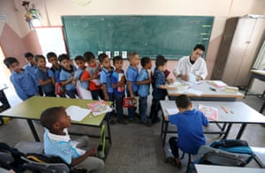 Mohammed Zurob marks a book for students at Taha Huseen elementary school