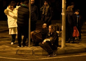 Group of residents sitting and standing on corner of street at night