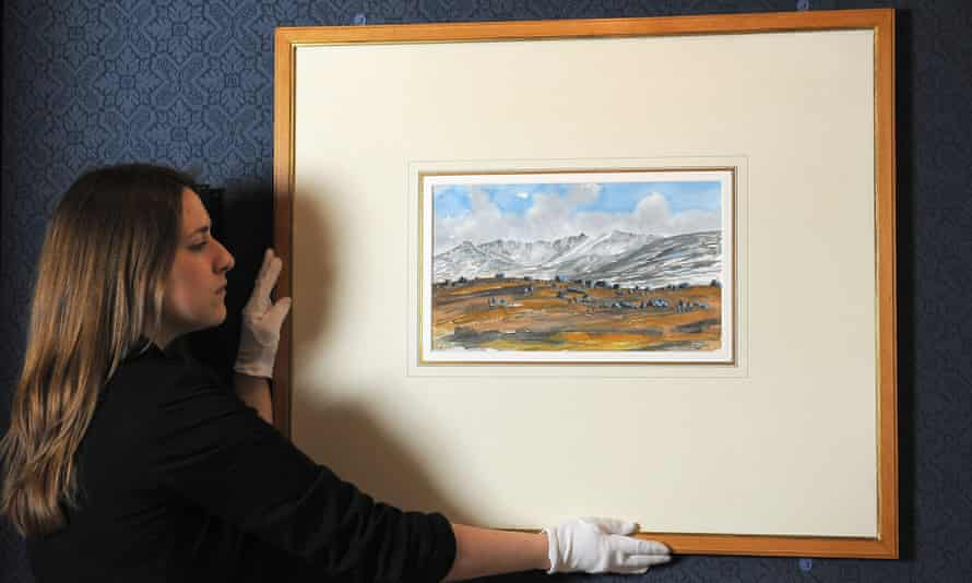 Exhibition Curator Lauren Porter adjusts a watercolour painted by Prince Charles in 2012 entitled Lochnagar from the Gelder Cottage