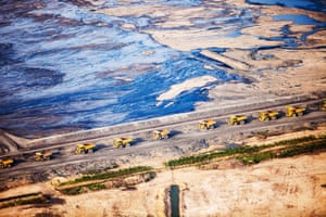 Alberta, Canada: Greed and destruction has turned this into a toxic wasteland. Above, dump trucks queue up to load with tar sands.