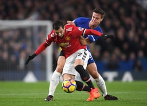 Henrikh Mkhitaryan holds back Cesar Azpilicueta as they battle for possession.