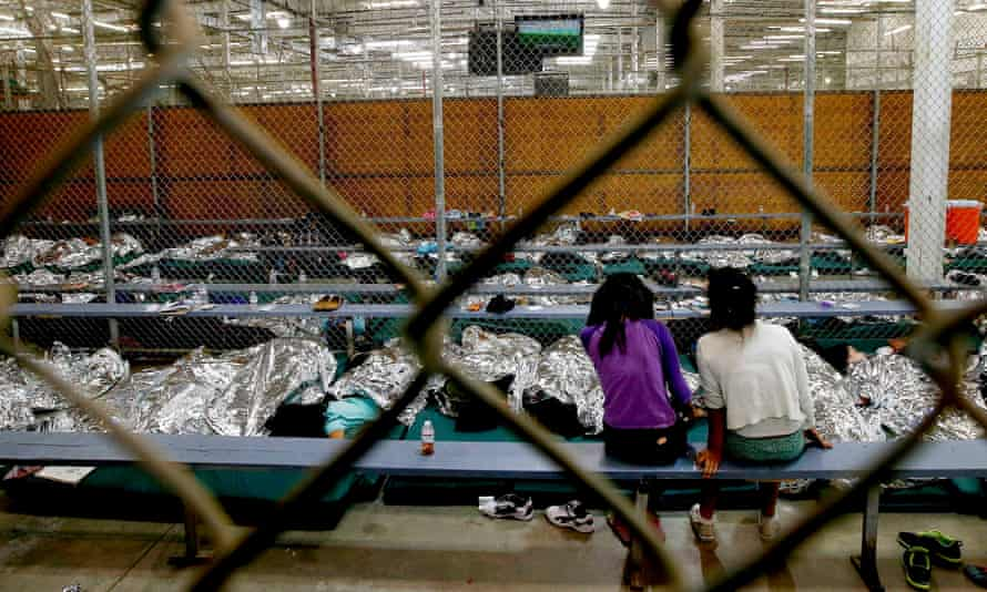Two girls watch a 2014 World Cup soccer match on a television from their holding area where hundreds of mostly immigrant children are being processed and held at the US Customs and Border Protection Nogales Placement Center in Arizona.
