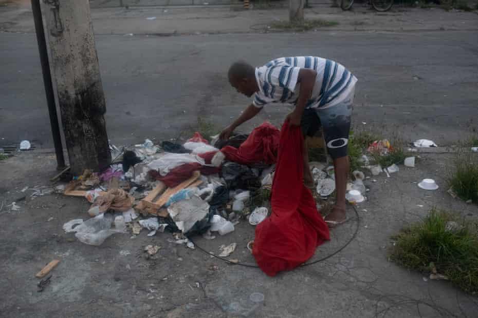 Valdemir dos Santos, un rezident fără adăpost de pe strada Regeneration, caută printre o grămadă de gunoaie biți care pot fi reciclați.