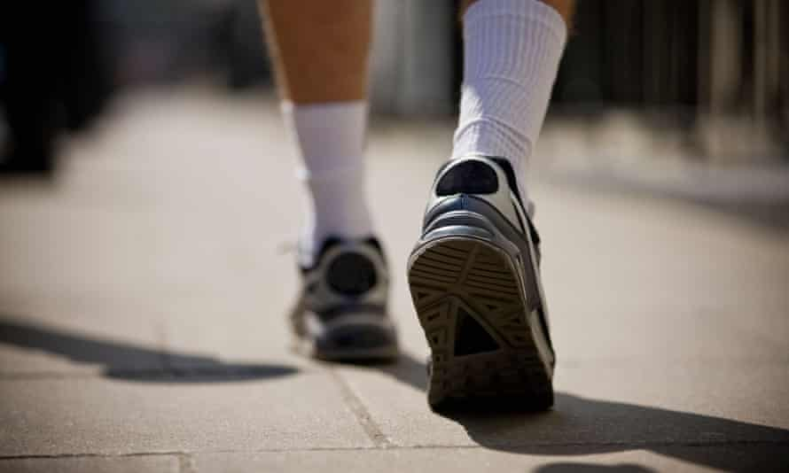 A close-up of a young man jogging in trainers